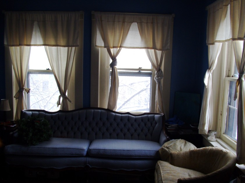 A room with a blue couch and a chair. The light is very low and fuzzy.