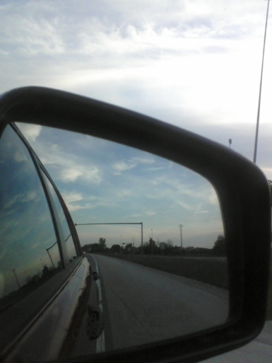 A view of the sunset in a car's rearview mirror