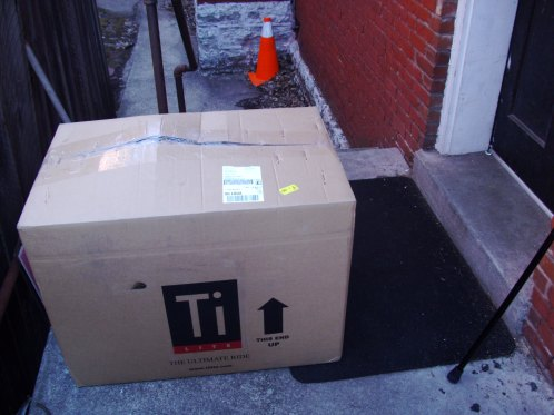 A large box labelled Ti. The box is sitting outside a doorway.